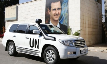 A poster of Syrian President Bashar al-Assad behind the vehicle of UN special envoy for Syria